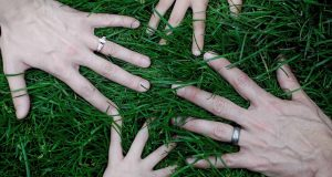 Four hands grasping the grass