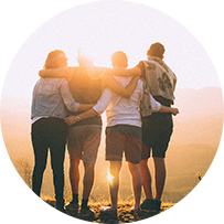 four people hugging looking at sunset